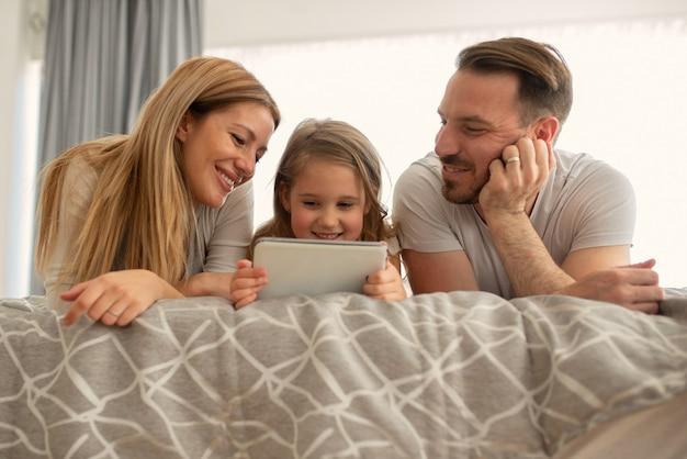 Glückliche kaukasische eltern lachen beim betrachten des tablet-bildschirms mit ihrer kleinen tochter