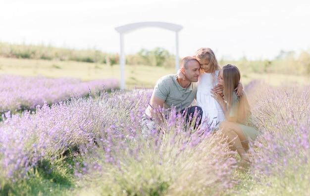 Glückliche kaukasische familie, die sich auf dem lavendelfeld ausruht, sich umarmt, zeit miteinander verbringt