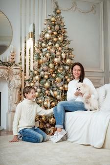 Glückliche kaukasische familienmutter und -sohn sitzen zu hause in der nähe des weihnachtsbaums mit ihrer kleinen hundefamilie ...