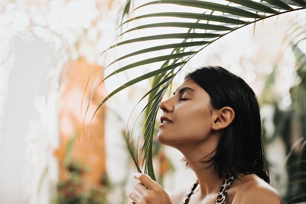 Glückliche kaukasische frau, die im exotischen resort aufwirft. außenaufnahme der blithesome frau, die palme schnüffelt.