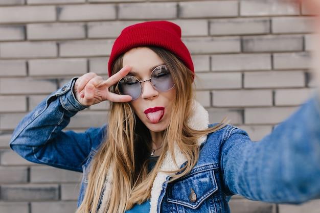 Glückliche kaukasische frau, die mit zunge heraus auf ziegelmauer aufwirft. attraktives mädchen im roten hut, das selfie mit geschlossenen augen macht.