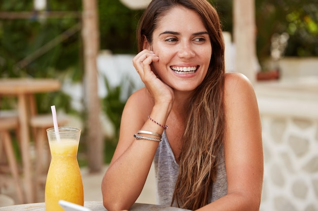 Glückliche kaukasische frau mit langen dunklen haaren, erholt sich in exotischer cafeteria mit frischem orangencocktail, hält smartphone