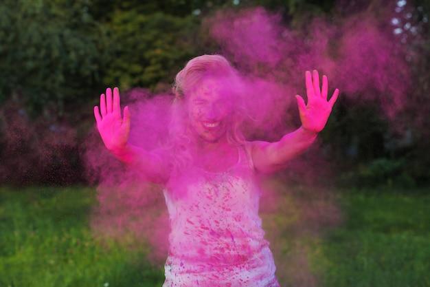 Glückliche kaukasische frau mit lockigem haar, die in einer wolke aus rosafarbener trockenfarbe posiert und das holi-festival feiert
