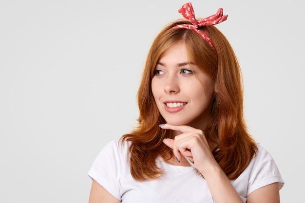 Glückliche kaukasische frau mit positivem lächeln, hält kinn und schaut gerne beiseite, trägt stilvolles stirnband
