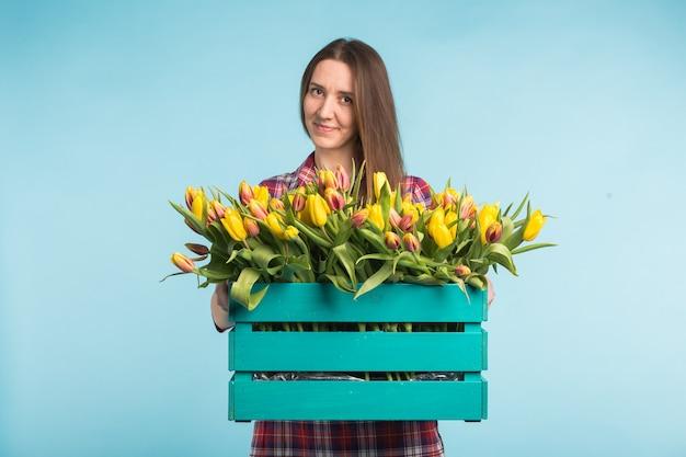 Glückliche kaukasische junge frau, die kasten mit tulpen auf blauer oberfläche hält