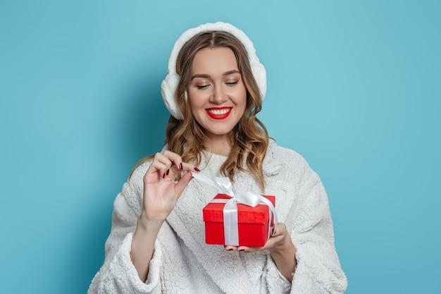 Glückliche kaukasische junge frau in pelzkopfhörern, künstlicher weißer pelzmantel mit roten lippen öffnet eine rote geschenkbox und zieht ein weißes band