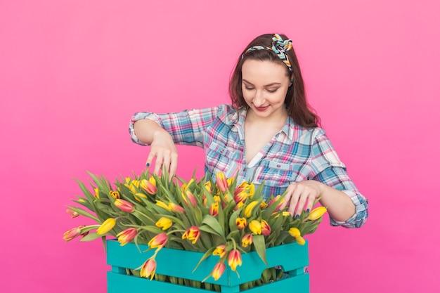 Glückliche kaukasische junge frau mit schachtel der gelben tulpen auf rosa oberfläche