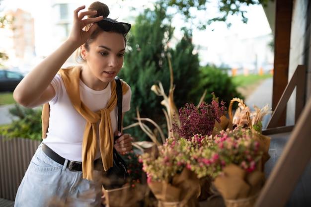 Glückliche kaukasische junge frau wählt topfblumen, um sie am gartenstand im freien zu kaufen