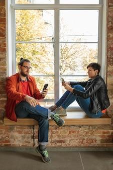 Glückliche kaukasische junge leute, paar hinter dem backsteinfenster. teilen sie nachrichten, fotos oder videos von smartphones, laptops oder tablets, spielen sie spiele und haben sie spaß. social media, moderne technologien.