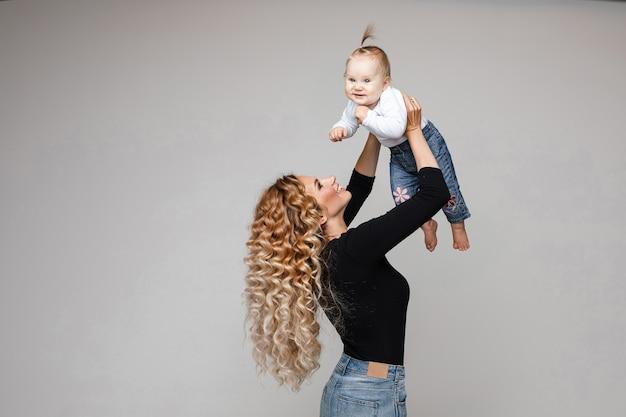 Glückliche kaukasische mutter mit dem langen gewellten haar, das niedliches baby mit einem schwanz oben in ihren armen auf grauem hintergrund hält.