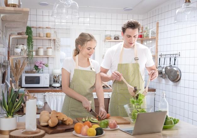 Glückliche kaukasische paarfamilie, die in der modernen küche mit laptop zu hause mit liebe kocht. verheirateter romantischer mann und frau, die frischen gemüsesalat kochen. gesundes lebensstilkonzept.