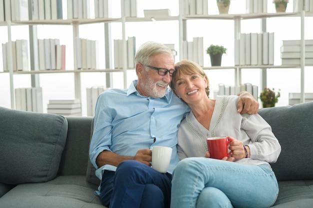 Glückliche kaukasische seniorenpaare trinken kaffee im haus, entspannungs- und gesundheitskonzept.