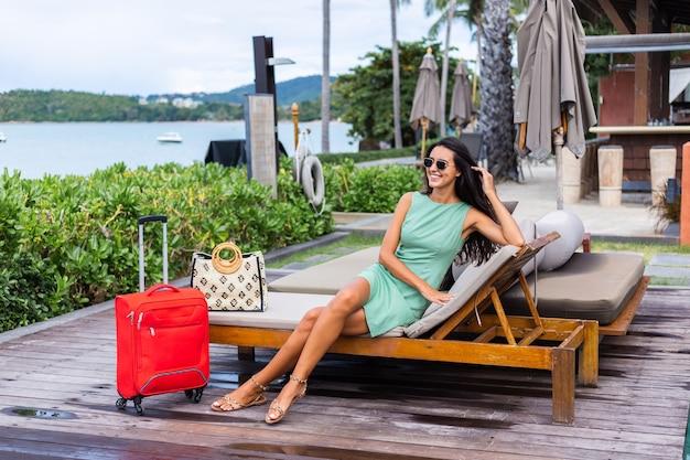 Glückliche kaukasische ziemlich lange haar elegante touristenfrau im kleid mit rotem koffer außerhalb des hotels