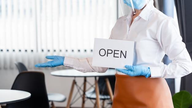 Glückliche kellnerin mit schützender gesichtsmaske, die offenes zeichen für die wiedereröffnung in ihrem restaurant hält