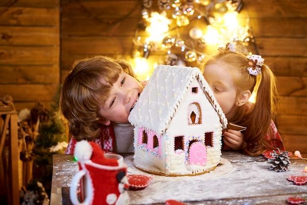 Glückliche kinder beißen weihnachtslebkuchen in einem verzierten raum für den feiertag.