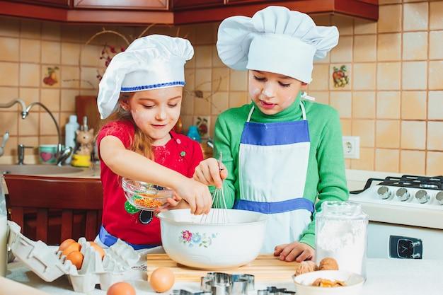 Glückliche kinder bereiten den teig vor
