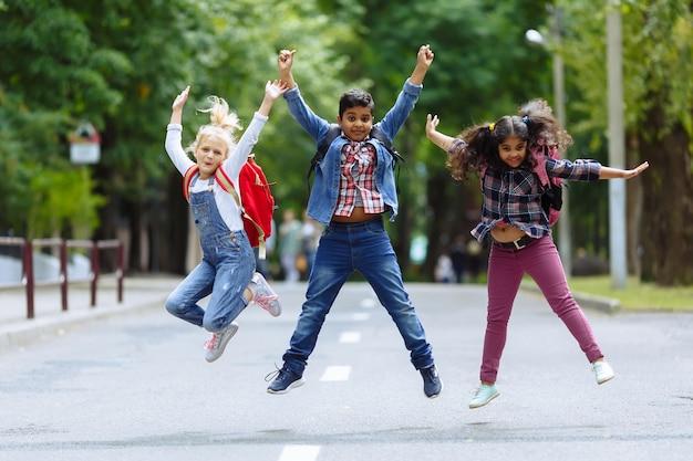 Glückliche kinder der mischrassengruppe, die in den park nahe schule springen