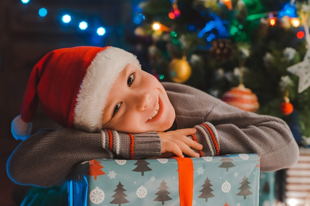 Glückliche kinder des kleinen jungen in sankt-hut mit geschenk haben weihnachten oder neues jahr.