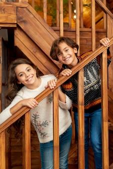 Glückliche kinder des mittleren schusses, die auf der treppe stehen