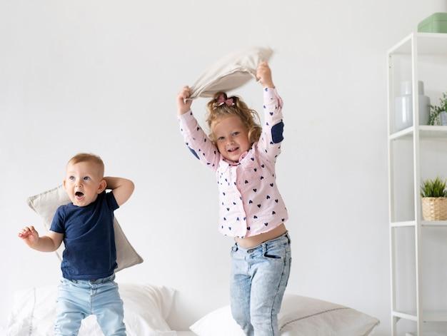 Glückliche kinder des mittleren schusses, die im schlafzimmer spielen