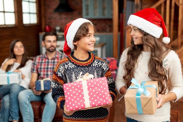 Glückliche kinder des mittleren schusses mit den geschenken, die einander betrachten