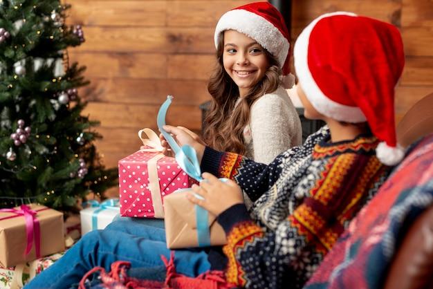 Glückliche kinder des mittleren schusses mit geschenken nahe dem weihnachtsbaum