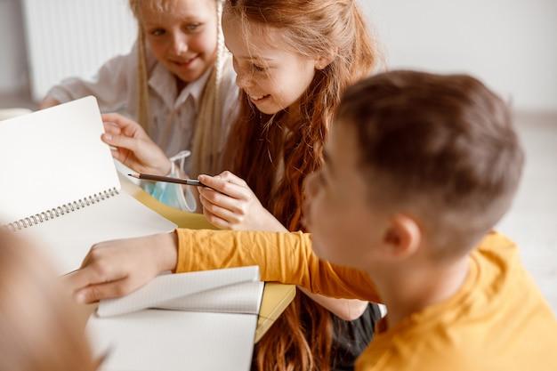 Glückliche kinder, die am tisch sitzen und notizbücher benutzen