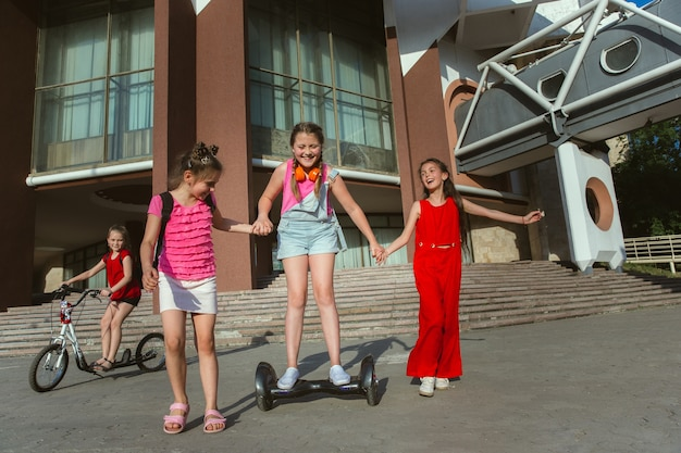 Glückliche kinder, die an der straße der stadt am sonnigen sommertag vor dem modernen gebäude spielen. gruppe von glücklichen kindern oder jugendlichen, die spaß zusammen haben. konzept der freundschaft, kindheit, sommer, ferien.