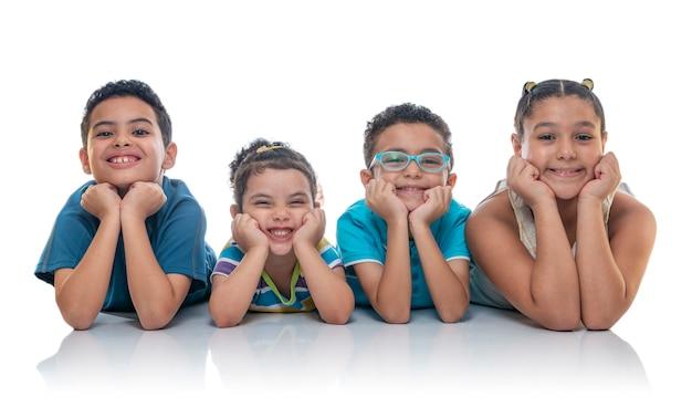 Glückliche kinder, die auf den boden aufwirft für foto legen