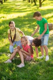 Glückliche kinder, die auf rasen im park spielen