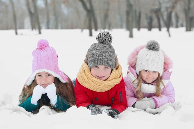 Glückliche kinder, die auf schnee liegen