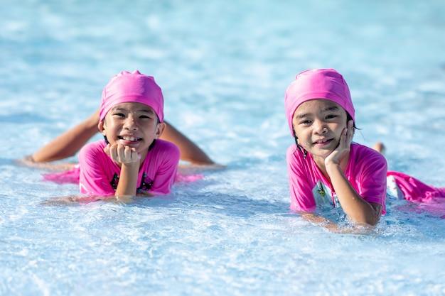 Glückliche kinder, die auf waterpark im swimmingpool smilling sind