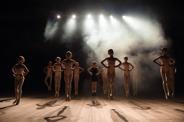 Glückliche kinder, die ballett machen, springen auf einer dunkel beleuchteten szene.