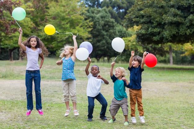 Glückliche kinder, die ballone halten