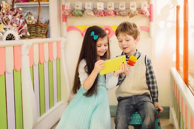 Glückliche kinder, die das tablett betrachten