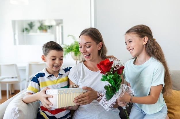 Glückliche kinder, die der mutter blumen schenken. schönen muttertag! kinder jungen und mädchen gratulieren lächelnder mutter, geben ihr blumenstrauß aus rosen und eine geschenkbox während der feiertagsfeier
