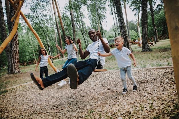Glückliche kinder, die eltern im park auf schwingen schwingen