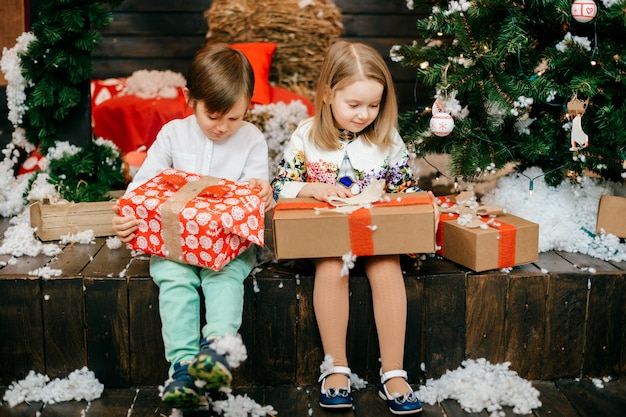 Glückliche kinder, die geschenkboxen im studio mit cristmas baum und dekorationen des neuen jahres öffnen.
