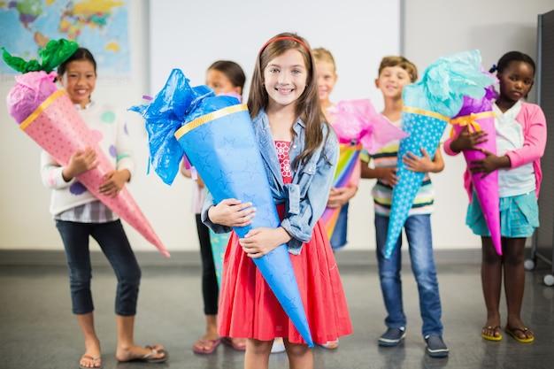 Glückliche kinder, die geschenke im klassenzimmer halten