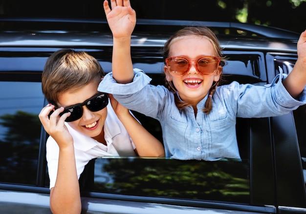 Glückliche kinder, die heraus das autofenster schauen
