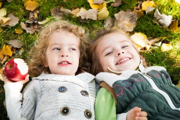 Glückliche kinder, die im herbstpark beim familienpicknick spielen