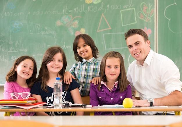 Glückliche kinder, die im klassenzimmer mit lehrer lernen