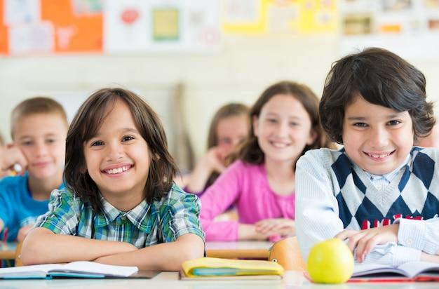 Glückliche kinder, die im schulklassenzimmer lernen