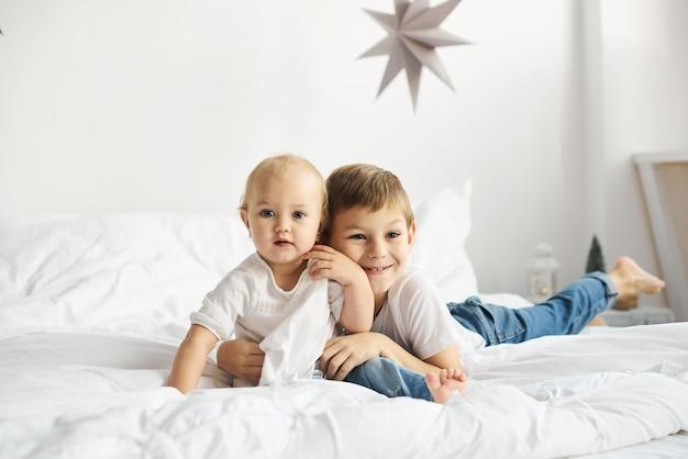 Glückliche kinder, die im weißen schlafzimmer spielen. kleiner junge und mädchen, bruder und schwester spielen auf dem bett.