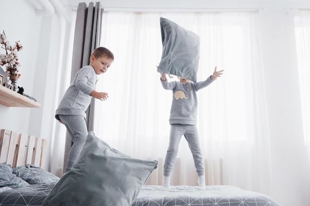 Glückliche kinder, die im weißen schlafzimmer spielen. kleiner junge und mädchen, bruder und schwester spielen im schlafanzug auf dem bett. nachtwäsche und bettwäsche für baby und kleinkind. familie zu hause.