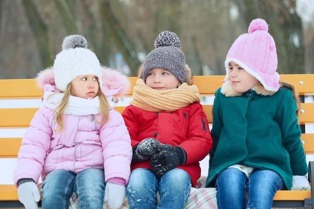 Glückliche kinder, die im winter draußen auf holzbank sitzen