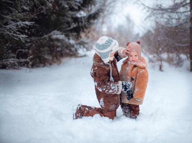 Glückliche kinder, die im winter im schnee spielen