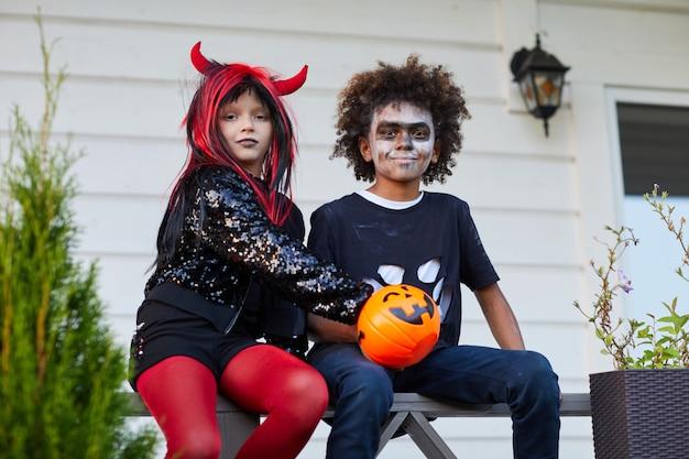 Glückliche kinder, die kamera an halloween betrachten
