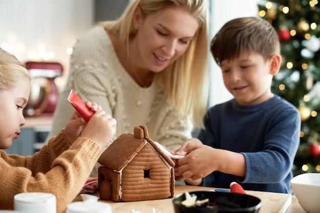 Glückliche kinder, die lebkuchenhaus mit ihrer mutter verzieren