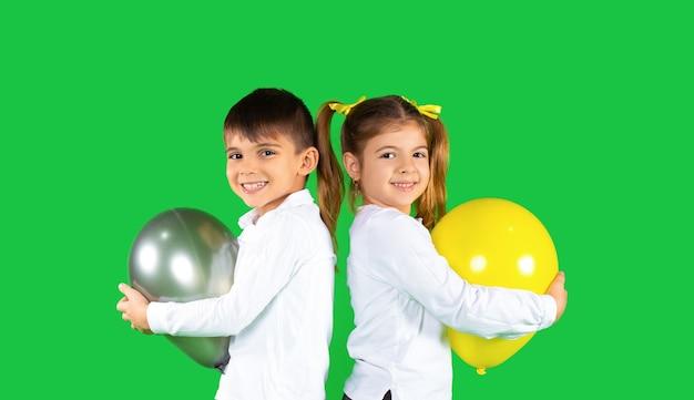 Glückliche kinder, die luftballons lächeln und umarmen